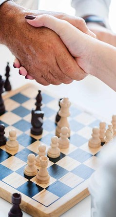 Two people shaking hands over a chess board