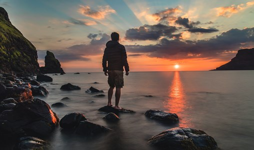 A man standing on a beach, looking at the sunrise